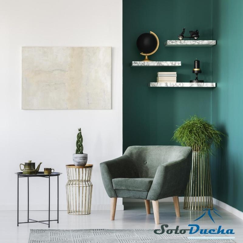 Espacio de lectura decorado con sillón y pared en tonos verdes.